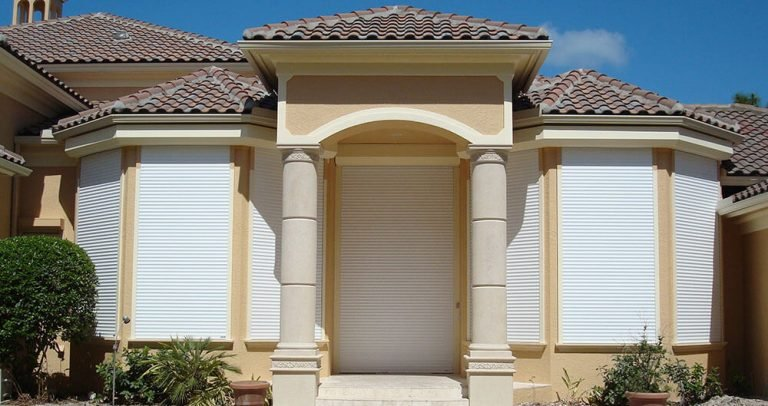 white roll down shutters on yellow Florida beach house